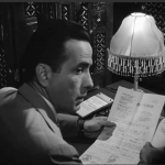 Photo of Rick (Humphrey Bogart) holding letter of transit in film, Casablanca (1942).